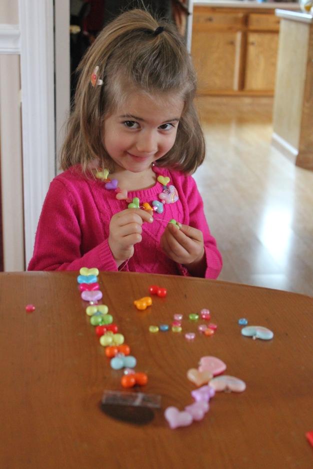 Faith making a friendship necklace for Noah